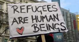 Protest sign with writing 'Refugees are human beings'