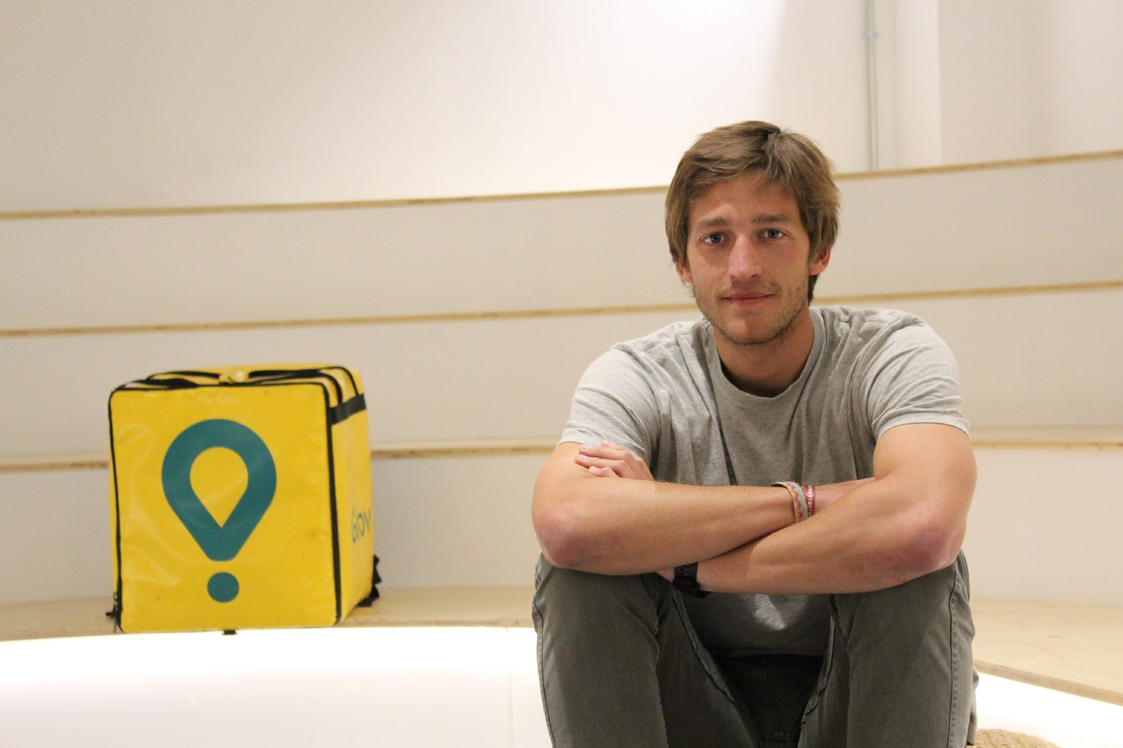 Glovo founder Oscar Pierre sitting on a set of stairs next to a Glovo delivery bag.