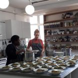 Photo of online supermarket Farmdrop's in-house chef Anneth serving up team lunch in the office kitchen.