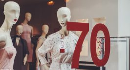 Mannequins in shop window with sale sign