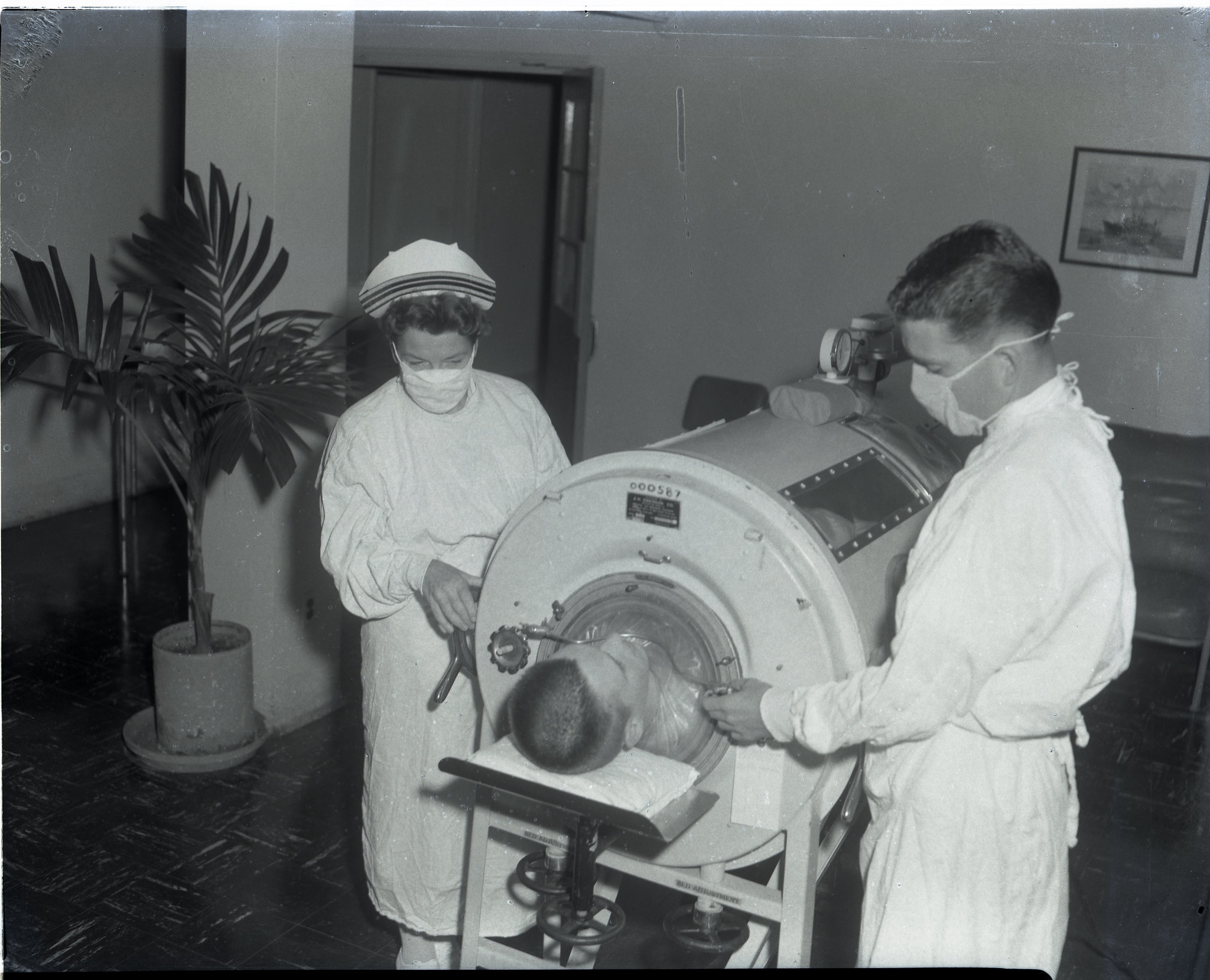 Image of a boy in an Iron Lung at the Naval Hosptial C 1960, and a doctor and a nurse standing around it. The Iron Lung was a healthcare innovation that saved many lives.