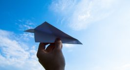 Paper airplane against a blue sky