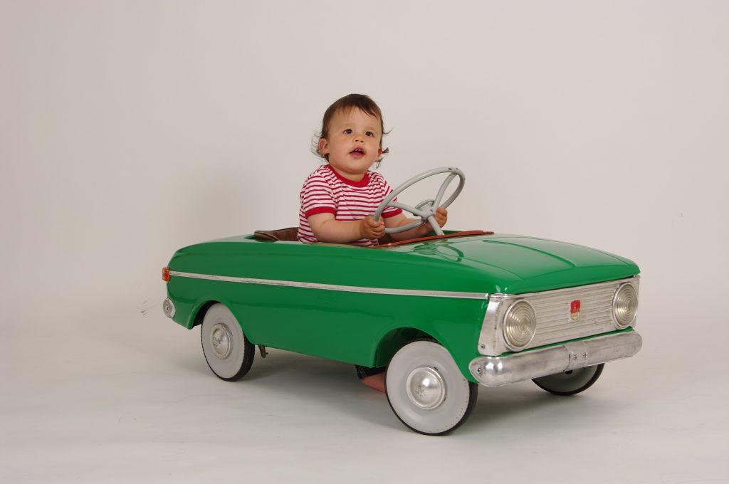 Child in a retro toy car