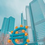A picture of a euro sign in front of skyscrapers.
