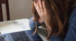 Picture of a student with her hands over her face next to a keyboard