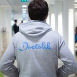 A photo of a man wearing a hoodie with the Doctolib logo