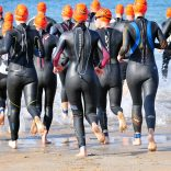Triathletes in orange hats run to the sea