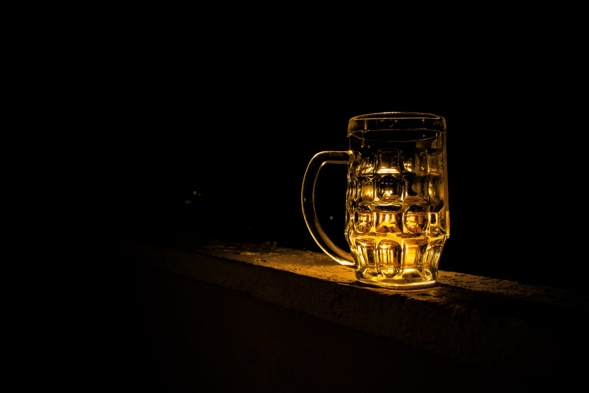 Glass of beer against a black backdrop