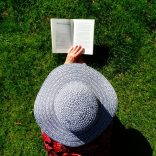 Woman in a hat reading a book on the grass