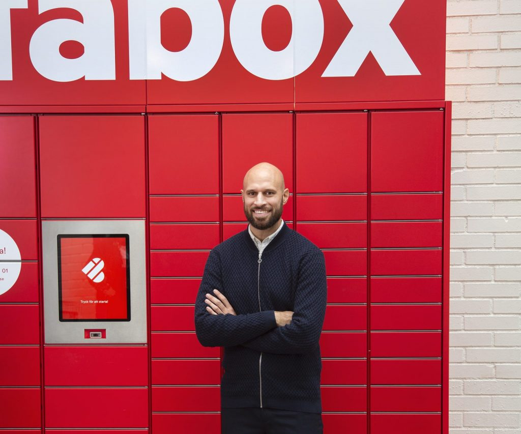 Alexis Priftis stands by Instabox lockers with delivery boxes