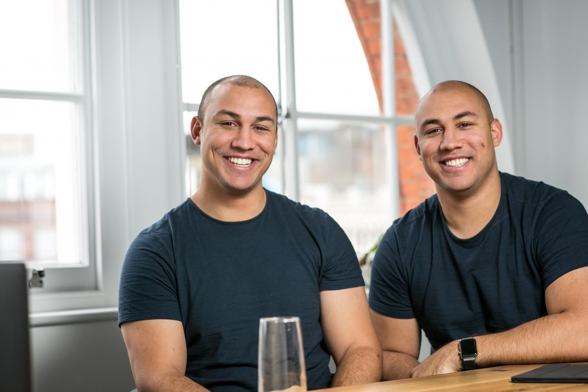 Marshmallow founders Oliver and Alexander Kent-Braham sit side by side at a table.