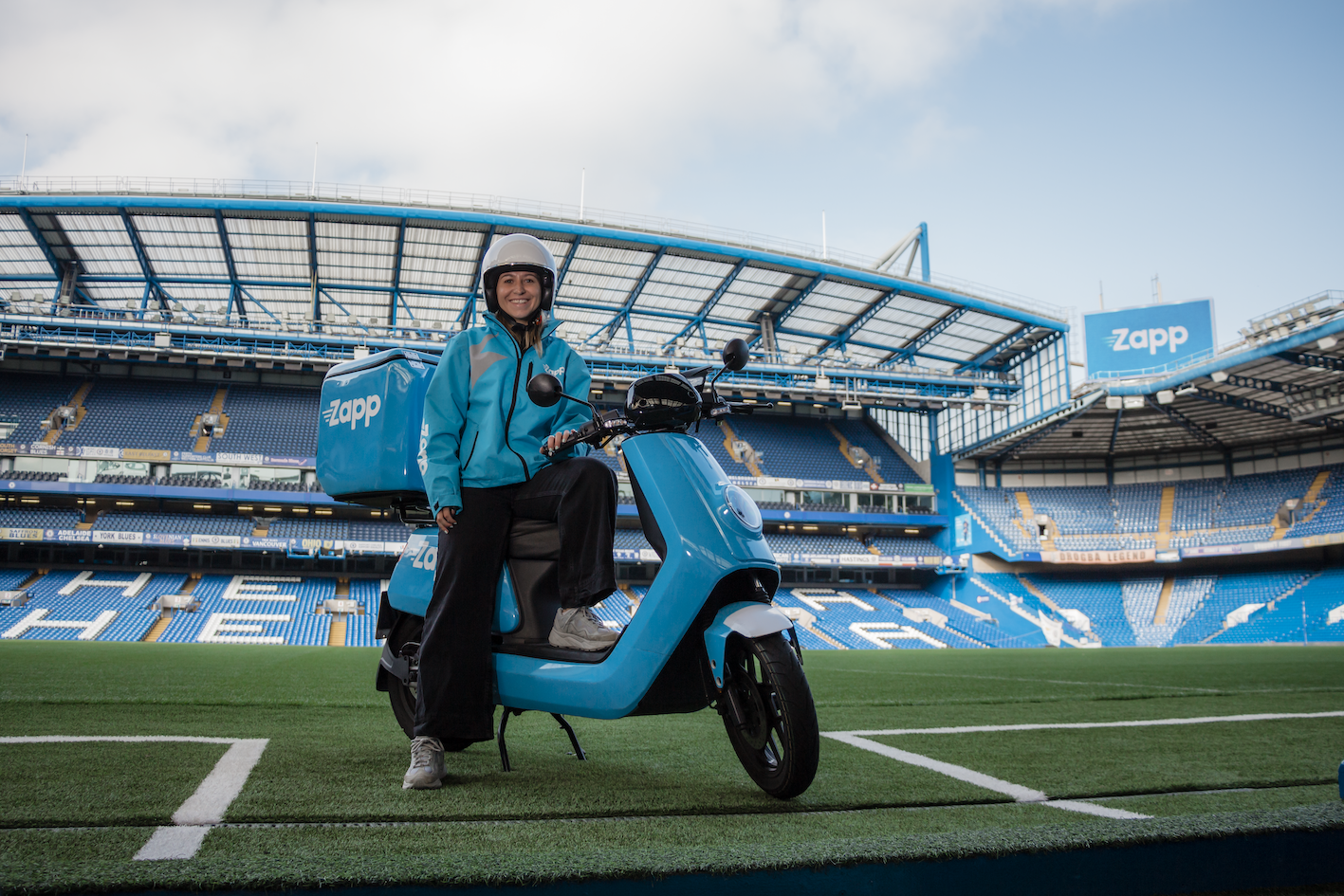 Zapp delivery driver sits on moped in Stamford Bridge
