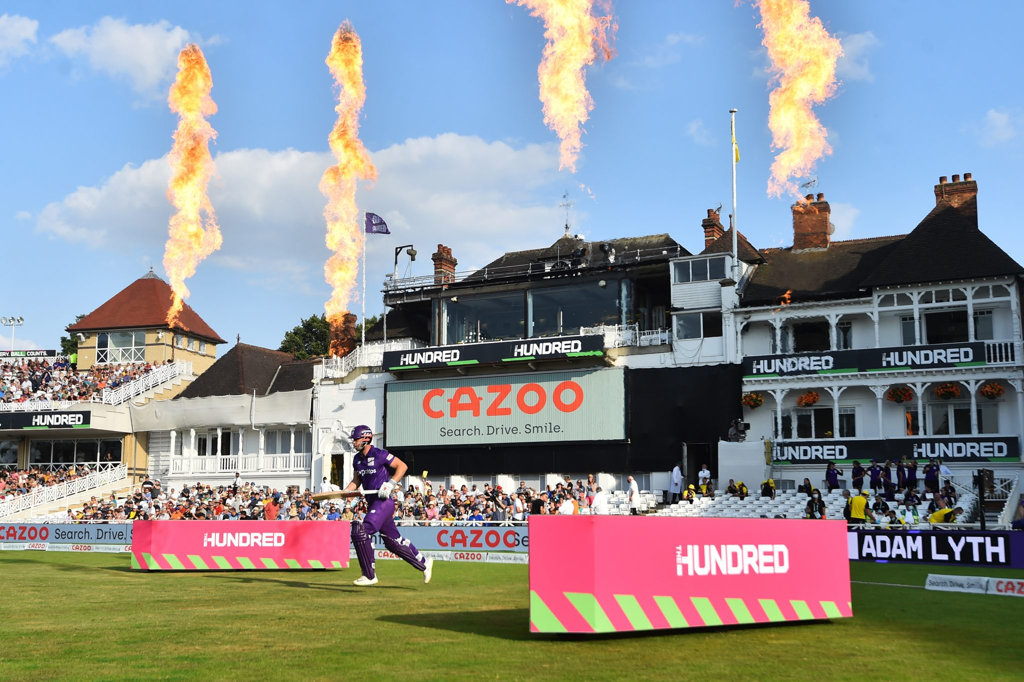 Cricketer runs onto pitch with Cazoo logo in the background.